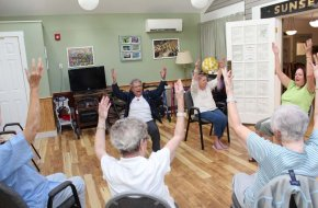Residents sing while they exercise